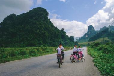 Les enfants font la course à vélo au Laos