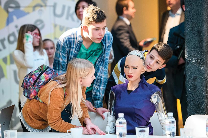 Des lycéens observant le robot humanoïde social Sophia, création de la société Hanson Robotics.
